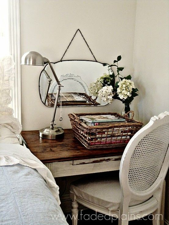 This is a really clever idea for a small bedroom...have a small table instead of a bedside table, it does triple duty -it's a bedside table, a home office and a vanity. I love the wicker back chair and the vintage mirror on the wall.