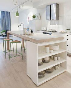 Meubles de cuisine blanche et plan de travail sur des pieds en chêne, simple et moderne comme îlot de cuisine.