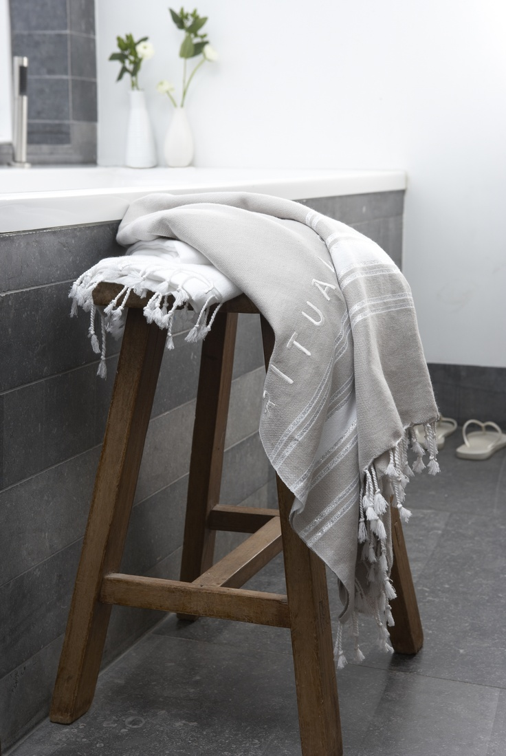 Wooden stool accenting dark grey and white bathroom