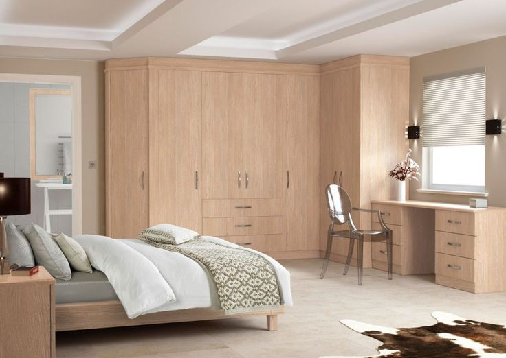 Idyllic Fitted Bedroom Design with Brown Grains Wood Four Door Three Center Drawers Wardrobe also Brown Grains Wood Six Drawers Study Desk Plus Black Transparent Chair and White Roll Up Window Blinds and Brown Grains Wood Frame Bed and White Pattern Traditional Sheet Bed