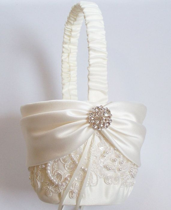 This ivory matte satin basket decorated with pearled and sequined alencon lace and an ivory satin sash cinched by a crystal centering at the handles is very elegant and perfect for a traditionalist bride. It is called the Miranda basket and is available from JLWeddings on Etsy.