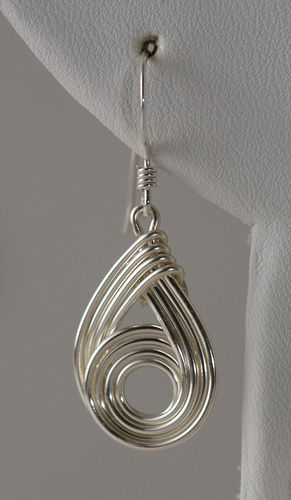 "Pendant and earrings made using ""Wirely"" wire weaving technique when multiple wires are woven together and keep the form with tension.  Earrings and pendant are made of artistic wire with sterling silver earwire."