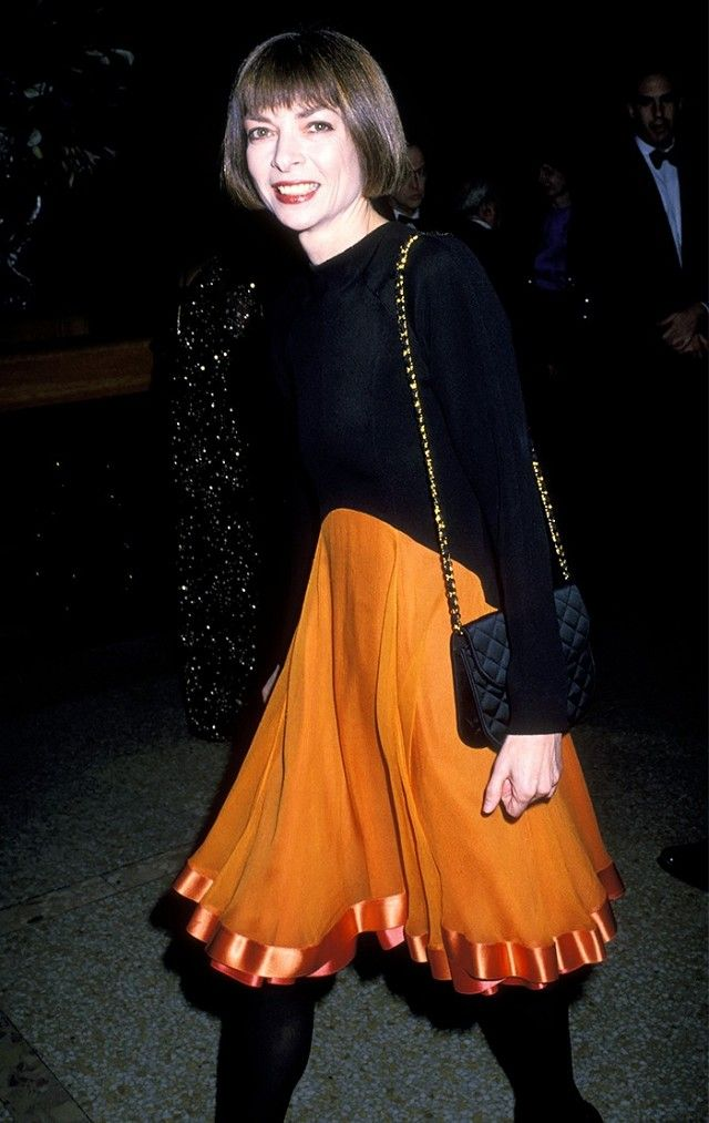 A young Anna Wintour wears a black sweater, orange skirt, quilted bag, and black tights