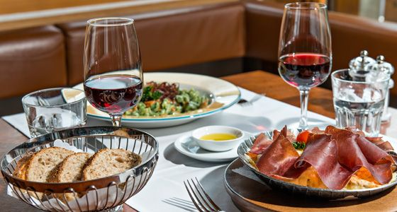 Fine glass of wine and table filled with finest food.Hotel with its friendly service and management. Everything at #billigehotelBerlin #LowbudgetHotelsinberlin  #CheapBudgetHotelsBerlin #BookBudgetHotels #berlin #staywacation