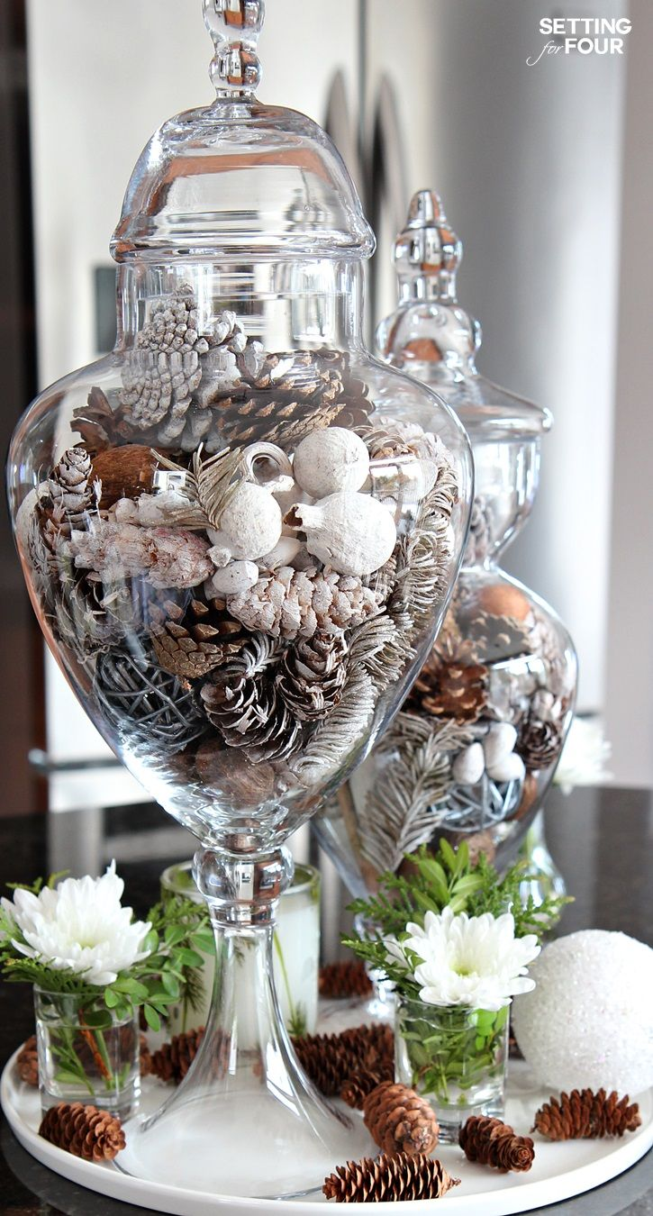 Decorate your kitchen in a jiffy with a beautiful centerpiece using apothecary jars! Apothecary jars filled with seasonal vase fillers are an easy and inexpensive way to add color and accessorize a neutral kitchen. Display one or a collection of them on your kitchen island, counter top or kitchen table!