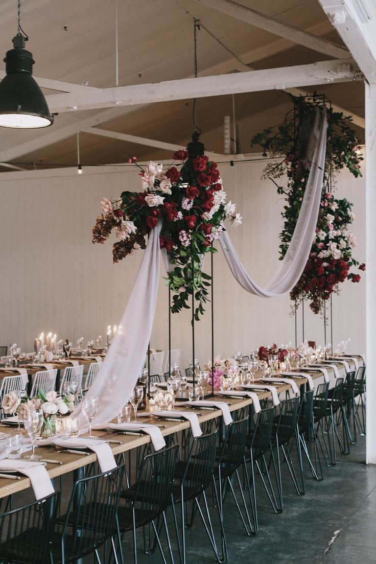 Warehouse wedding designed and styled by Nomad Styling. Hanging floral installation with draped fabric table runners. Wire chairs for a modern feel at Gather and Tailor.