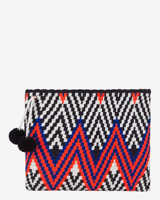 Sophie Anderson Lia Zig Zag Fabric Zip Top Clutch: The color way on this holiday-ready clutch is vibrant and uplifting. Hand-woven from cotton with double pom detail. Zip top. Measures: 11 1/2 by 9 1/4 . Unlined. In navy/white/orange. Made in ...