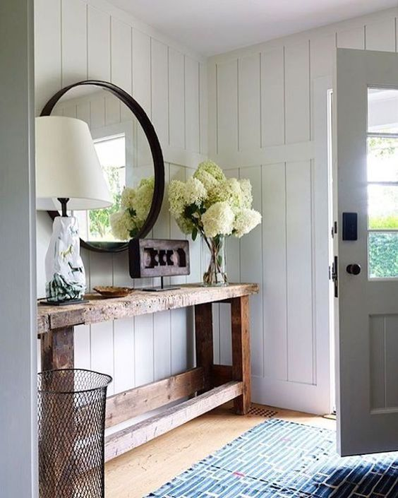 Modern farmhouse entryway with reclaimed wood console, round mirror and white shiplap walls.