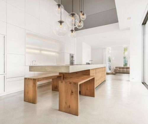 The concrete and oak kitchen island harmonizes with the camouflaged two-story wall unit