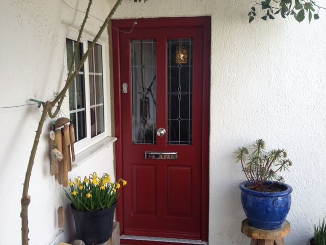 Hardwood timber entrance door in dual colours - the interior is white and the exterior is Hampstead Red. The glass is flower green style