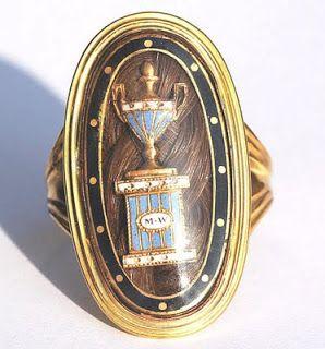 Anello che contiene un'urna smaltata  recante le iniziali del defunto e appoggiata su un torchon di capelli