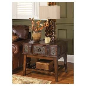 Satisfy your taste for something delightfully different with this campaign-style end table. Details including inset stamped metal and buckled belt accents provide such a well-traveled touch, while the decadent hue is rich with contrast and character. Signature Design by Ashley is a registered trademark of Ashley Furniture Industries, Inc.