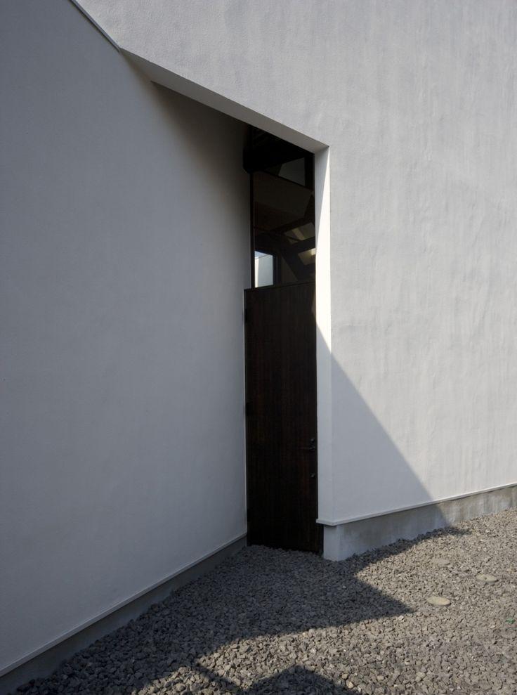 斜めの壁との隙間は玄関ドアがあり、上部は硝子の欄間窓となっています。<br /> シンプル 専門家:石川淳が手掛けた、玄関ドア(オウチ01・狭小二世帯住宅)の詳細ページ。新築戸建、リフォーム、リノベーションの事例多数、SUVACO(スバコ)