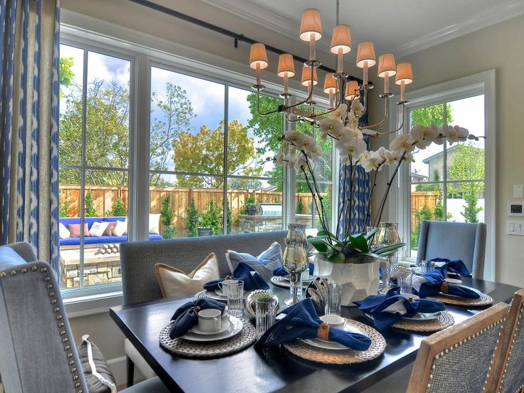 Varied fabrics and textures in shades of blue come together to provide a look of beauty and feeling of peace in this open dining space. A chandelier with 10 mini lamps hangs above the table, which is surrounded by upholstered armchairs.
