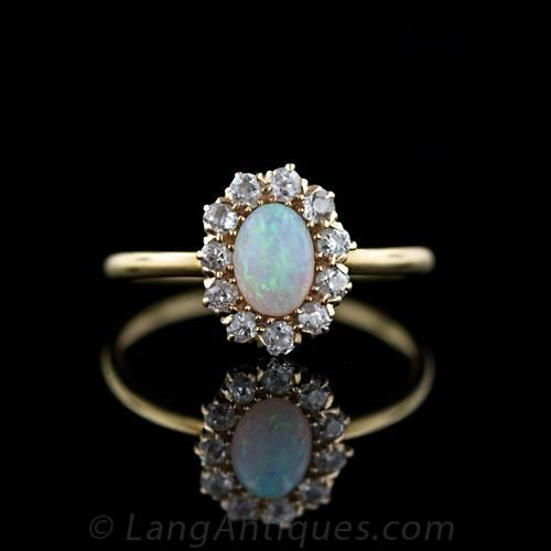 A little sweetheart of an antique opal and diamond ring. The center opal weighs about 3/4 of a carat and is surrounded by .40 carats of old-mine cut diamonds. The opal glows with predominantly blues and and greens with orange highlights. A classic Victorian treasure.