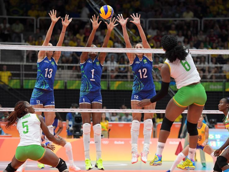 Brazil outside hitter Sheilla Castro de Paula Blassioli (13), middle blocker Fabiana Claudino (1), and weak side hitter Natalia Pereira (12) work to block a shot by Cameroon weak side hitter Laetitia Crescence Moma Bassoko during their game in the preliminary round in the Rio 2016 Summer Olympic Games at Maracanazinho.  Kirby Lee-USA TODAY Sports