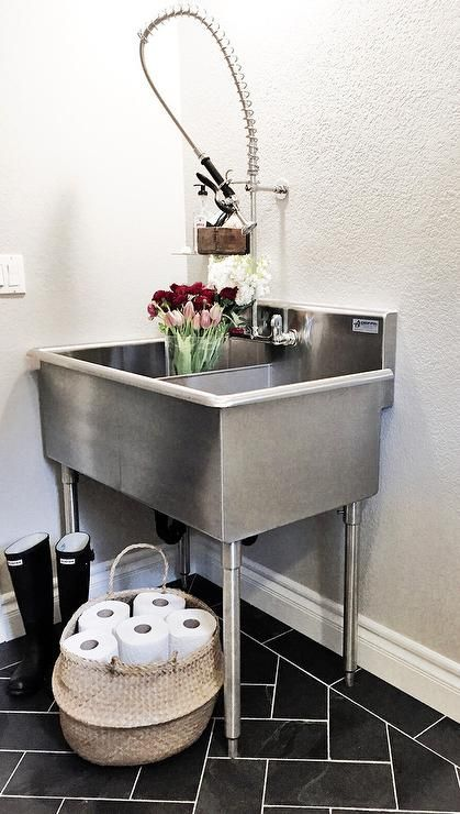 Laundry room features a freestanding stainless steel dual utility sink paired with a pull-out faucet atop a black slate herringbone tile floor.
