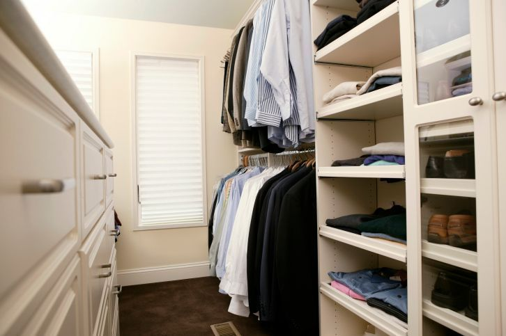 A cream and white walk-in closet with several storage options including double-hung rods, pull out trays, and deep drawers. What do you think of the shoe storage?
