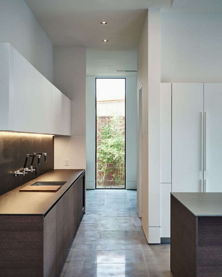 This kitchen defines sleek with a full length window at the end of the hall, handless drawers, and no accessories.