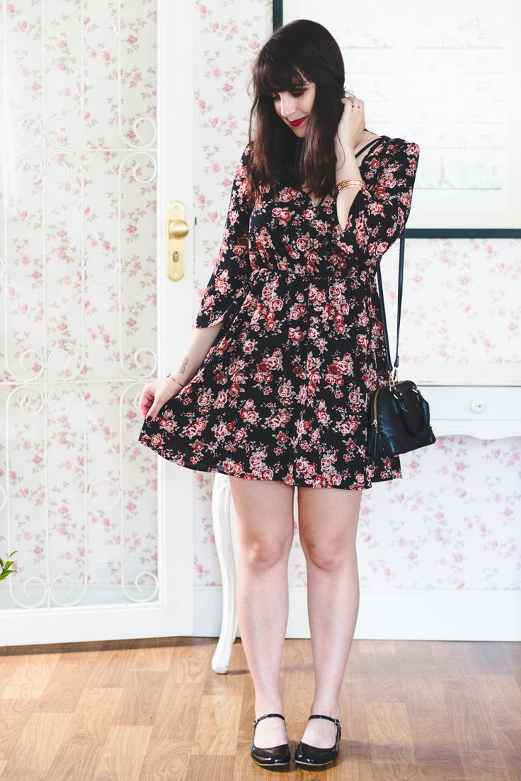 Melina Souza com look romântico. Vestido floral (fundo preto e flores em tons de rosa e vermelho), bolsa pequena preta e estruturada e sapatilha estilo boneca preta de verniz.
