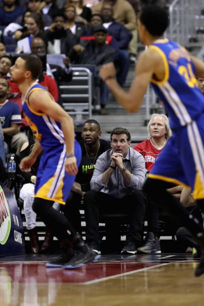 Stephen Curry of the Golden State Warriors follows the play against the Washington Wizards as Under Armour founder Kevin Plank watches from the...