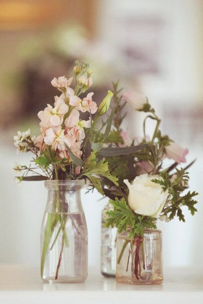 mismatched bottles with flowers and greenery - vintage style wedding