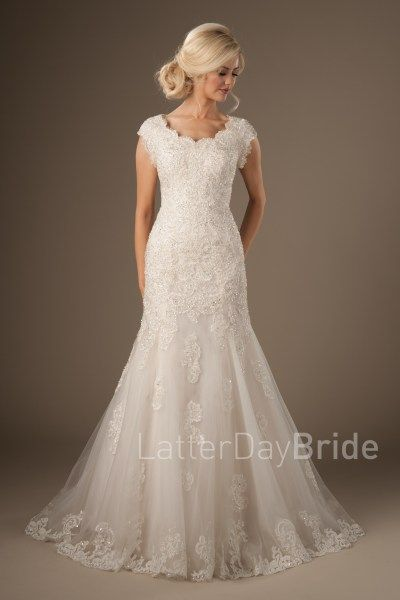 Silverthorne | Bridal pizzazz at its best! Take a look at this one of a kind, bedazzled wonder. From the scalloped neckline and sleeves, to the flattering mermaid shape, this gown is certainly a knock out!    Style Love: The trailing beaded appliques throughout the skirt and train are a huge hit with this gown! The all beaded lace is dazzling us all.    Gown available in Ivory/Pink Champagne (as pictured) or White.    Find at LatterDayBride.com and in Store in SLC, UT