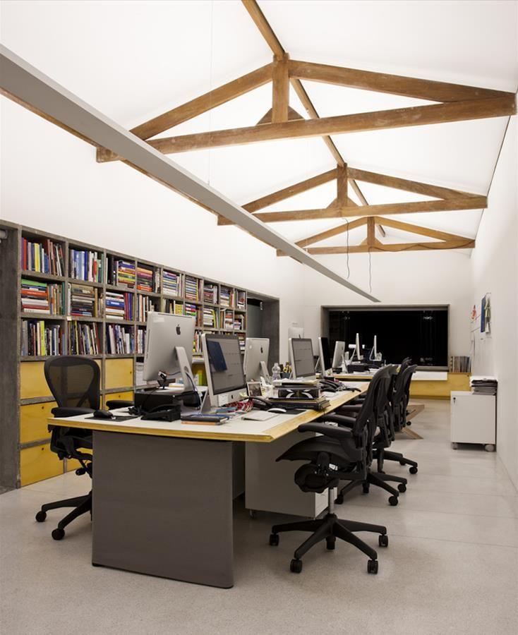 Com planta livre nos dois pavimentos, antiga casa se adéqua à realidade de um ateliê e escritório a partir de um programa simples, que tem como elementos principais a grande estante de concreto aparente e os acessos independentes