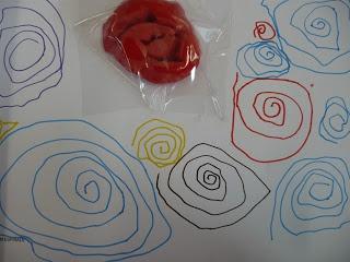 """Inicialment fer amb plastilina """"un xurro"""" i cargolar-lo. Reproduir-ho en el paper amb retoladors prims de colors."""