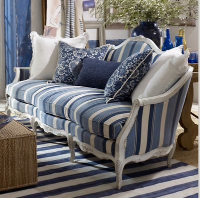 blue & white by Ralph Lauren ~ I like this for a beach house.  I have a sofa almost exactly like this only there is wicker on the sides. Mine is painted white, too but has a more formal striped upholstery and multiple brocade and velvet and many colors  But this is another way of decorating, and I do enjoy blue.