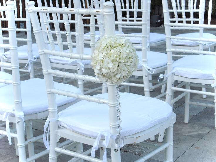 Hydrangeas kissing flowers hung from white chiavari chairs
