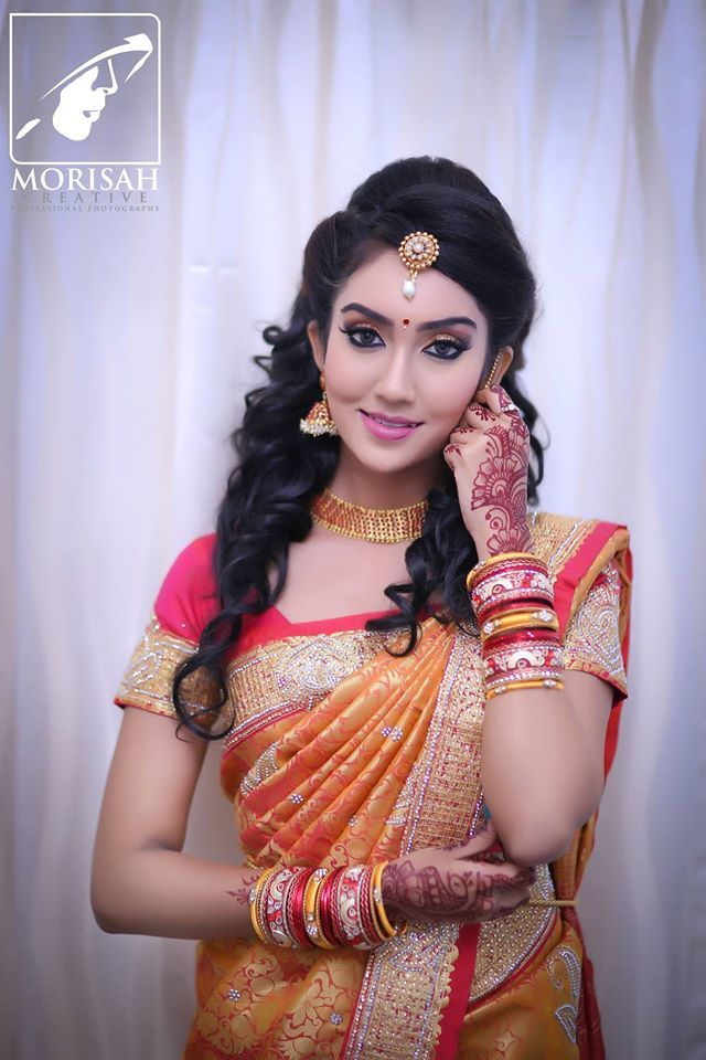 South Indian bride. Gold Temple jewelry. Jhumkis.Orange red silk kanchipuram sarees.Half up half down curled hair do with tikka. Tamil bride. Telugu bride. Kannada bride. Hindu bride. Malayalee bride.Kerala bride.South Indian wedding.