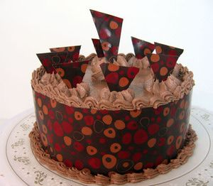 Learn how to wrap a cake with chocolate. This step-by-step photo tutorial will show you how to use transfer sheets to wrap a cake in chocolate and create chocolate cut-outs to decorate the top of your cake.: Finish Your Cake