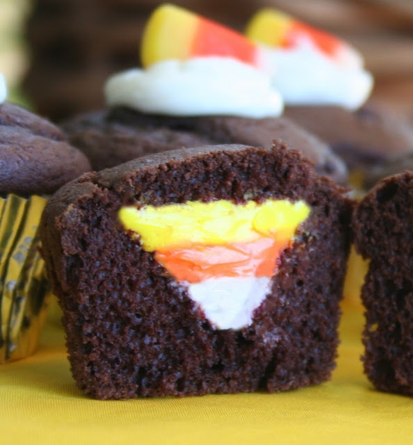 Candy corn cupcake--umm yumm!  Take the top off of cooked cupcakes, cut out a little hole, fill it with frosting layers, re-top, and decorate!  Pretty!
