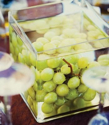 Simple grape centerpieces. Make a little fancier by tying a ribbon around the glass container (keep ribbon in place using scrapbooking glue dots)?