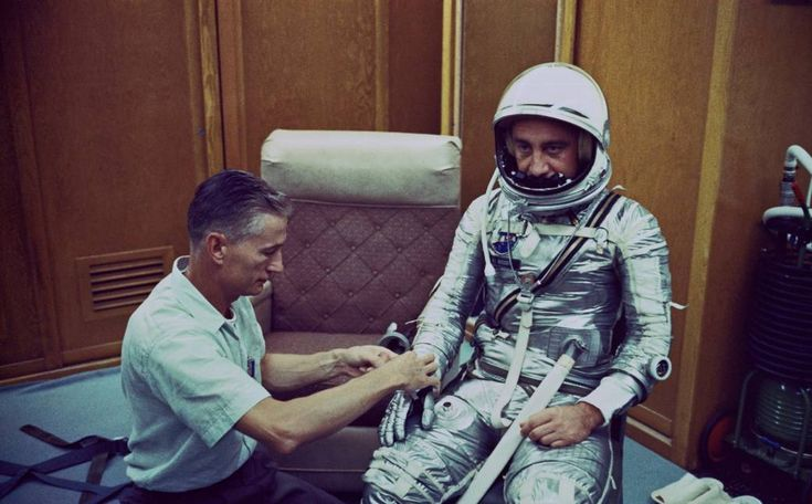 """Donning a spacesuit for the Mercury-Redstone 4 mission, astronaut Virgil I. """"Gus"""" Grissom chats with spaceflight equipment specialist Joseph W. Schmidt in the personal equipment room of Hangar S at Cape Canaveral, Fla."""