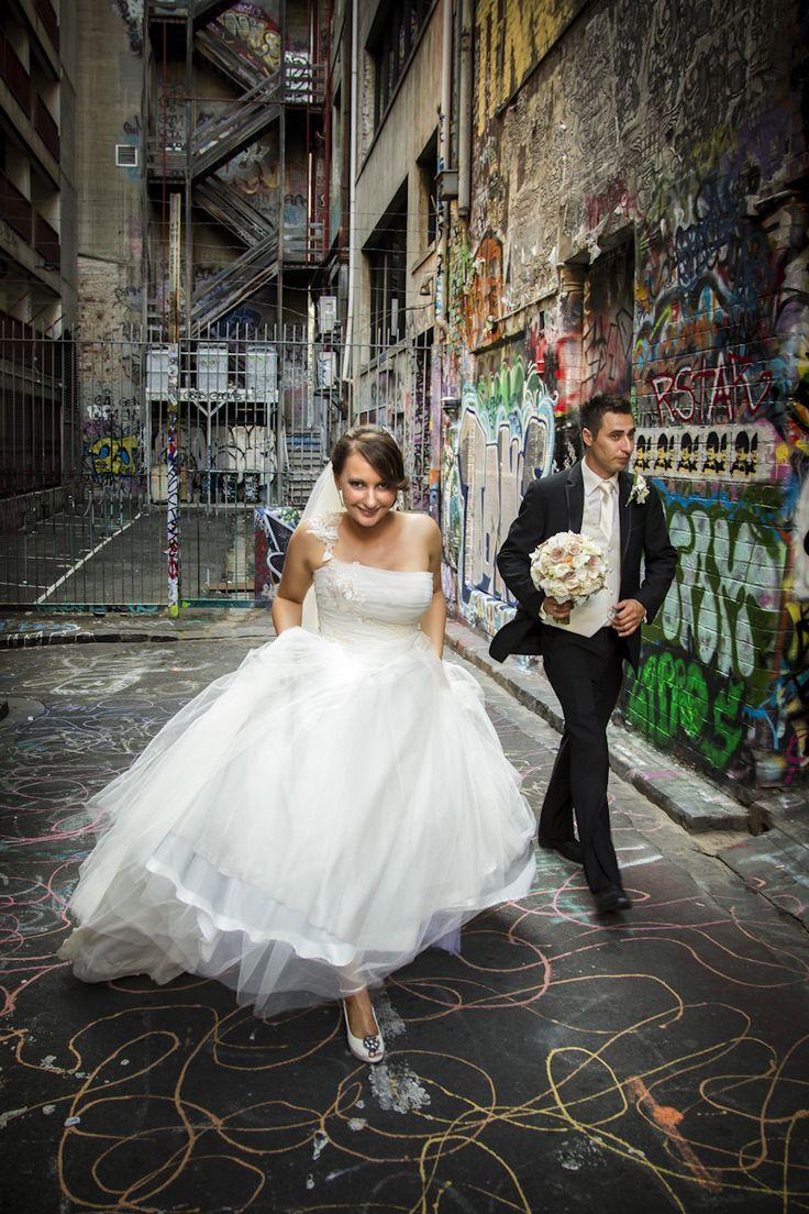 Bride and Groom, candid shot in Hoser Lane with graffiti.  http://www.whitepoint.com.au/wedding-photographer-melbourne.html #hosierlane #graffiti