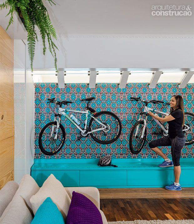 """""""Um jeito bonito de guardar a bicicleta na sala. Pintados de azul, os ganchos de aço, onde se apóiam as bicicletas, se camufam no desenho do fundo. Cada um aguenta até 50 kg. Nada de bagunça à vista: os equipamentos ficam nos gavetões (40 cm de profundidade). Juntos, os quatro compartimentos alcançam 3,50 m de comprimento."""""""