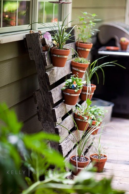 Use a pallet to hang your flower pots. Fun idea! Leaned against the garden shed?