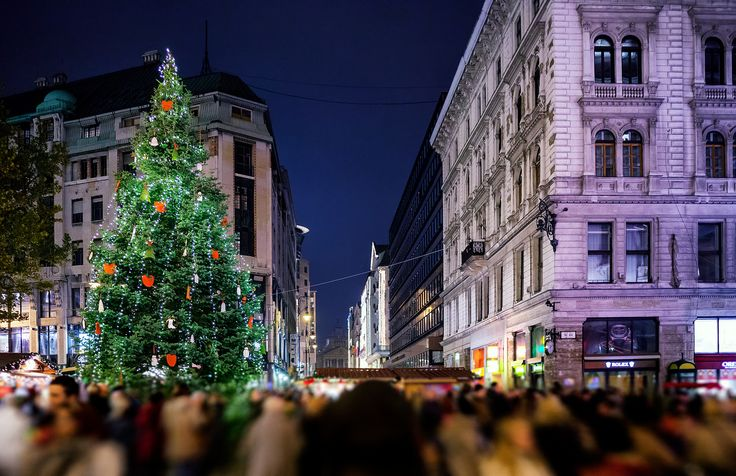 A crowd of people enjoy the #Christmas #market in #Budapest. It is an authentic Christmas market, with traditional foods and drinks at Vörösmarty Square.