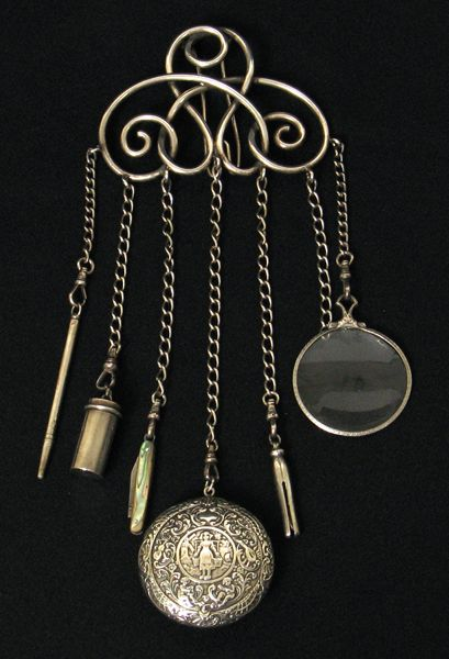 "Chatelaine is French for ""mistress of the castle""    In the 18th and 19th centuries, women in charge of their estates wore a decorative clip of long chains holding important household items about the waist. These items were things like the key to a pantry where valuable tea, spices and food were kept; a small notebook; sewing items; a magnifying glass; or maybe a watch, nail file, or compass. The earlier waist-hung items were referred to as ""equipage"", later evolving t..."