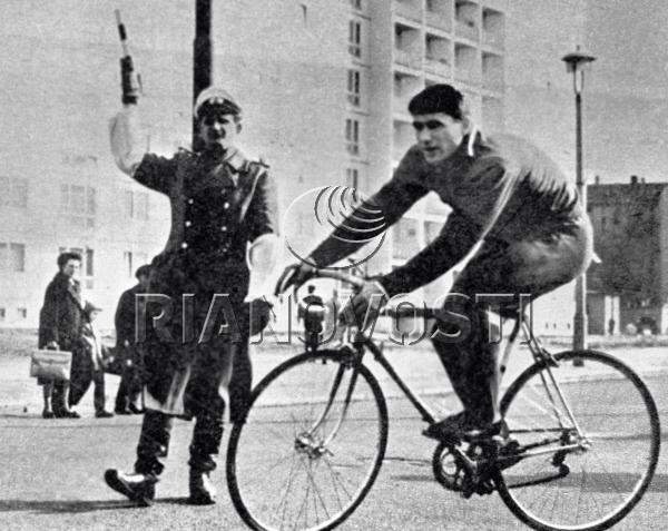 Сотрудник народной полиции Берлина пропускает советского чемпиона мира по велосипедному спорту Омара Пхакадзе, спешащего на тренировку. 1966
