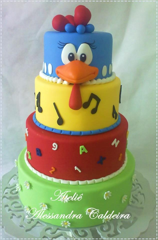 Blue, Yellow, Red,  Green 4 tiered #cake with a chicken on top ;)