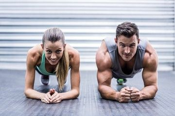 Muscular couple doing planking exercises
