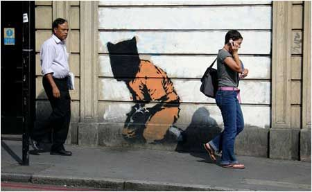 """Banksy Guantanamo Bay Prisoner Graffiti - London The war on terror was declared soon after 9/11. This Banksy piece is intended to highlight the """"secrer"""" war on terror that has taken place – primarily at Guantanamo Bay where terror suspects are detained. This Guantanamo Bay detainee in Islington is a less than subtle reminder that we do not live an entirely free society. The image has since been removed although its precise location in Islington is unknown."""
