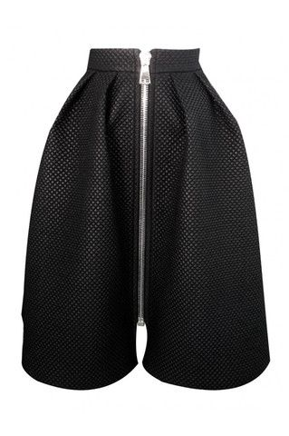 Black flared skirt with a front zipper. Keep the full silhouette in focus with a tucked-in blouse.