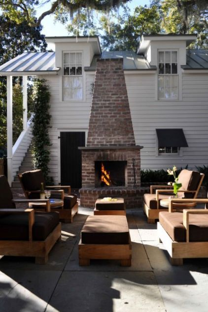 Brick backyard fireplace - This strong vertical focal point splits the tall, white wall of the nearby home, critical to making this outdoor living space cozy and comfortable.