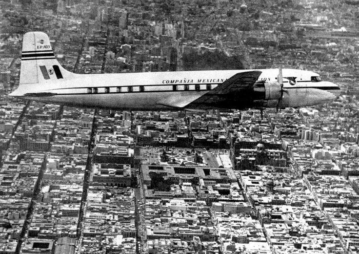 Vistosa fotografía de un avión de la Compañía Mexicana de Aviación surcando el cielo capitalino en los años cincuenta. Entre un mar de edificios, se alcanzan a distinguir la Plaza de la Constitución y la Catedral Metropolitana, y más allá, la Alameda Central.