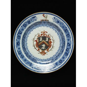 This dish, made in China in around 1730, was made by special order and exported to England. It is decorated with the coat of arms of an English family, the Skinners, and is part of a service made for one of three brothers: Richard, a London merchant, Matthew, Chief Justice of Chester, or Samuel, an East Indiaman captain killed by pirates in 1731 off the coast of India.