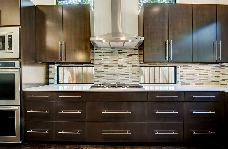 modern dark stained kitchen cabinets with glass backsplash